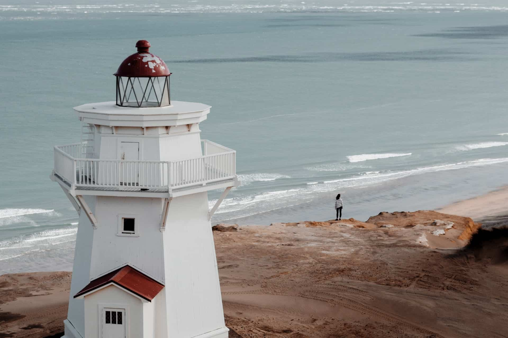 white concrete lighthouse near body of water during daytime